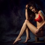 Women with amazig body in red lingerie on dark background.