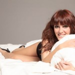 Smiling woman in lingerie in the bed